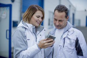 Malermeisterin Jessica Müller zeigt ihrem Mitarbeiter Ralph Müller auf dem Smartphone, was sie ihm sagen will.