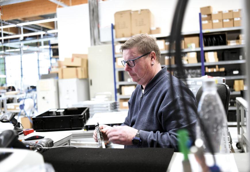 Ein Mitarbeiter der AfB sitzt in der Lagerhalle des Unternehmens an seinem Werktisch bearbeitet und konzentriert ein Computer-Bauteil, das er in der Hand hält.