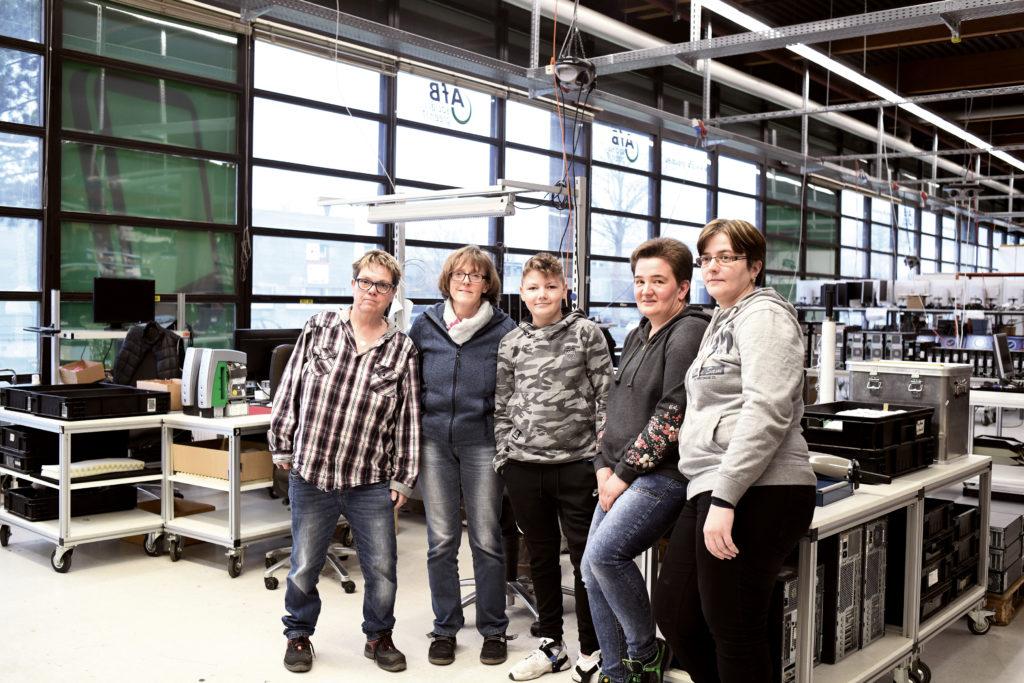 Einige Mitarbeiterinnen und ein junger Praktikant posieren in einer Reihe in der Halle der AfB für die Kamera. Links im Bild ist die Mitarbeiterin Jutta Dieckmann zu sehen.