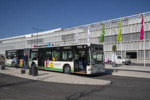 Ein Shuttlebus an einem Bussteig, im Hintergrund ein großes Parkhaus. Foto: BUGA Heilbronn 2019 GmbH