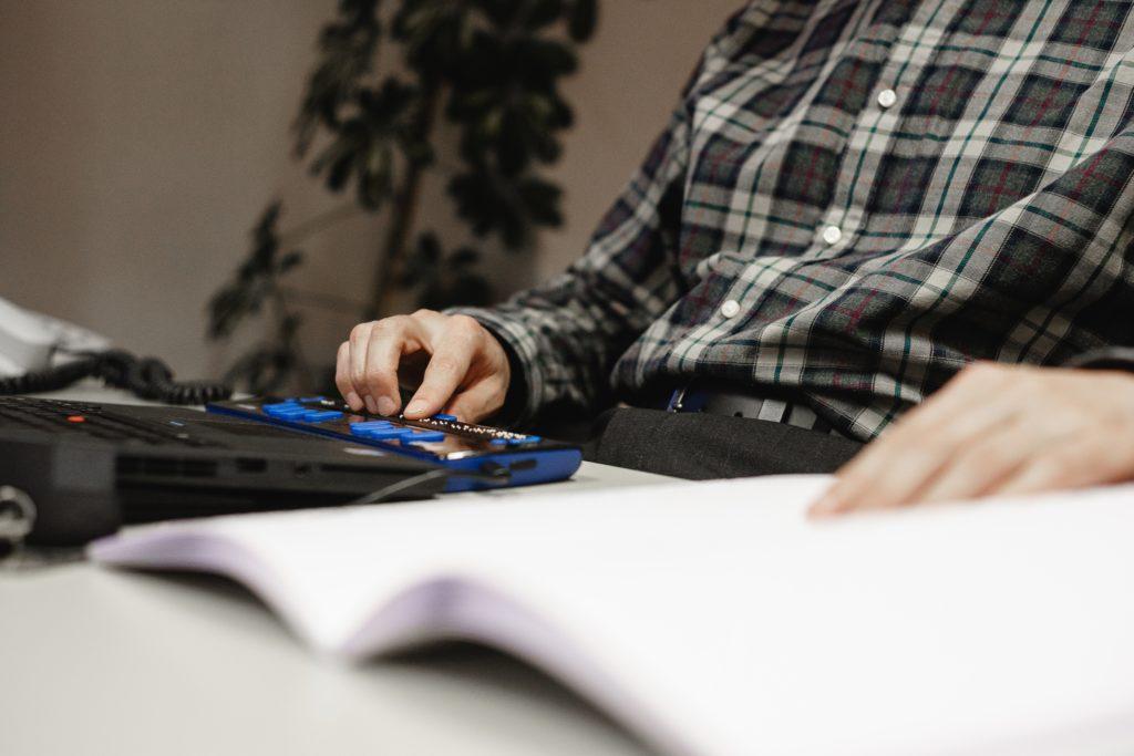 Ein Mann arbeitet mit einer Braille-Zeile an seinem Computer. Foto: Michel Arriens