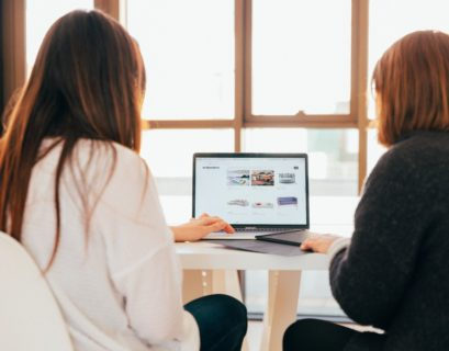Zwei Frauen sitzen in einem hellen Raum an einem Schreibtisch und schauen gemeinsam auf einen Laptop, auf dem eine Website aufgerufen ist. Beide sind nur von hinten zu sehen, dazwischen der Laptop..