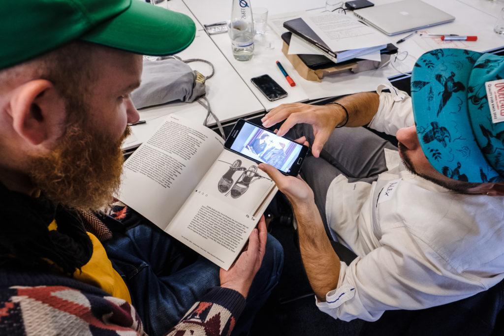 Zwei junge Männer schauen auf ein Smartphone, auf dem die App des Deaf Magazine aufgerufen ist.