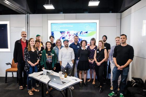 Gruppenfoto vor einer Leindwand: Die Finalisten und Organisatoren der Challenge.