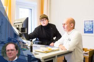 Ein Mitarbeiter mit Schwerbehinderung an seinem Büro-Arbeitsplatz, zusammen mit einem Kollegen.