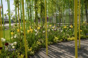 Buntes Blumenbeet aus Tulpen und anderen Blumen, dazwischen ragen lange, gelbe Stäbe auf. Foto: BUGA Heilbronn 2019 GmbH