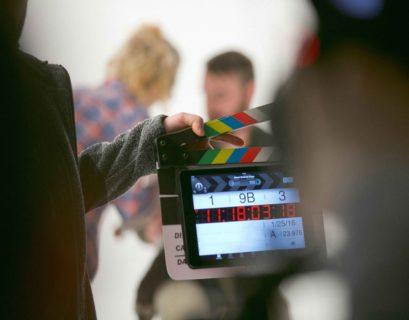 Blick auf eine Filmklappe, dahinter eine Filmszene mit zwei Menschen vor einem hellen Hintergrund.