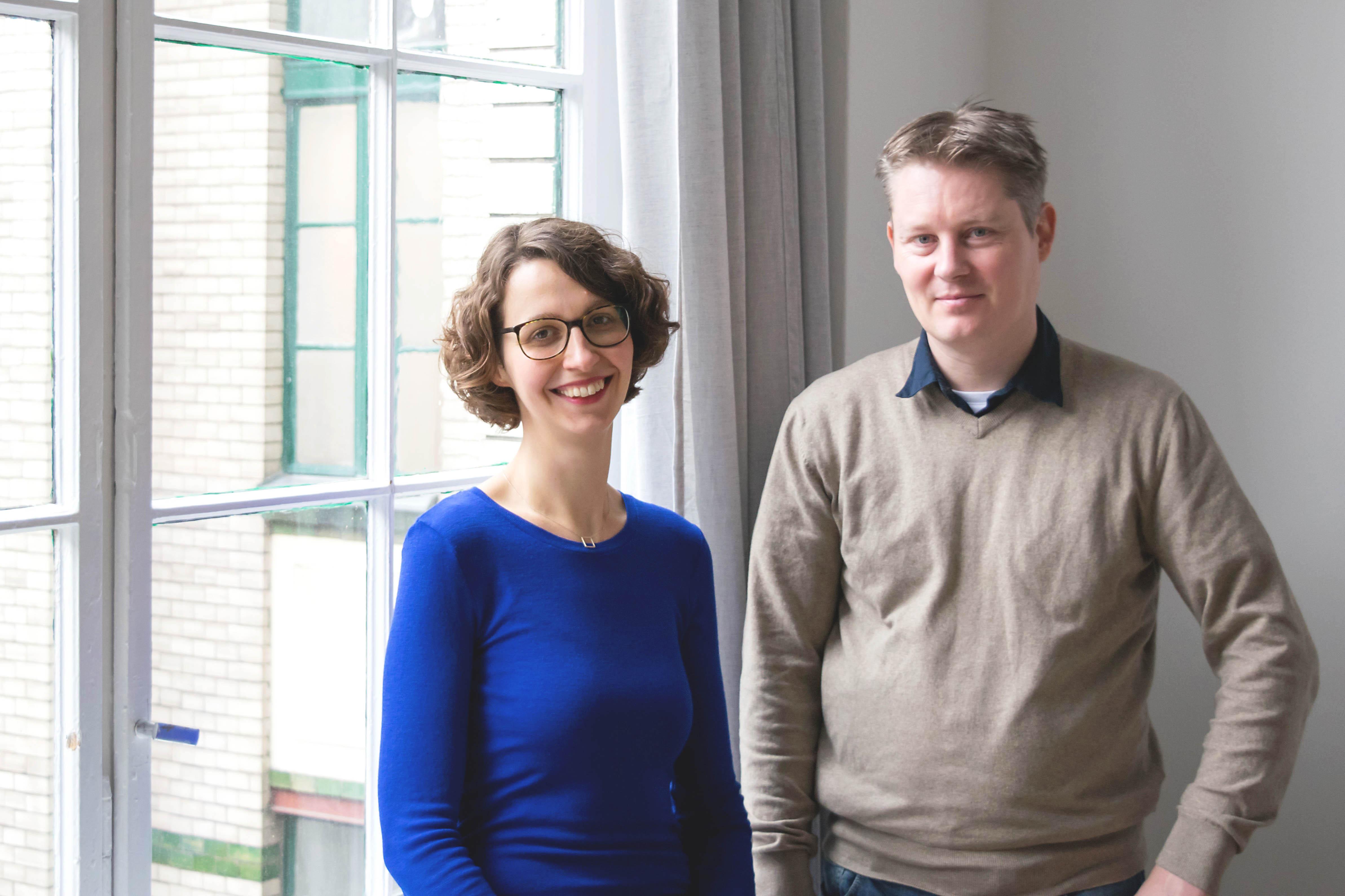 Sally Ollech (links) und René Kuhlemann (rechts) stehen in einem hellen Büro von Diversicon und lächeln in die Kamera.