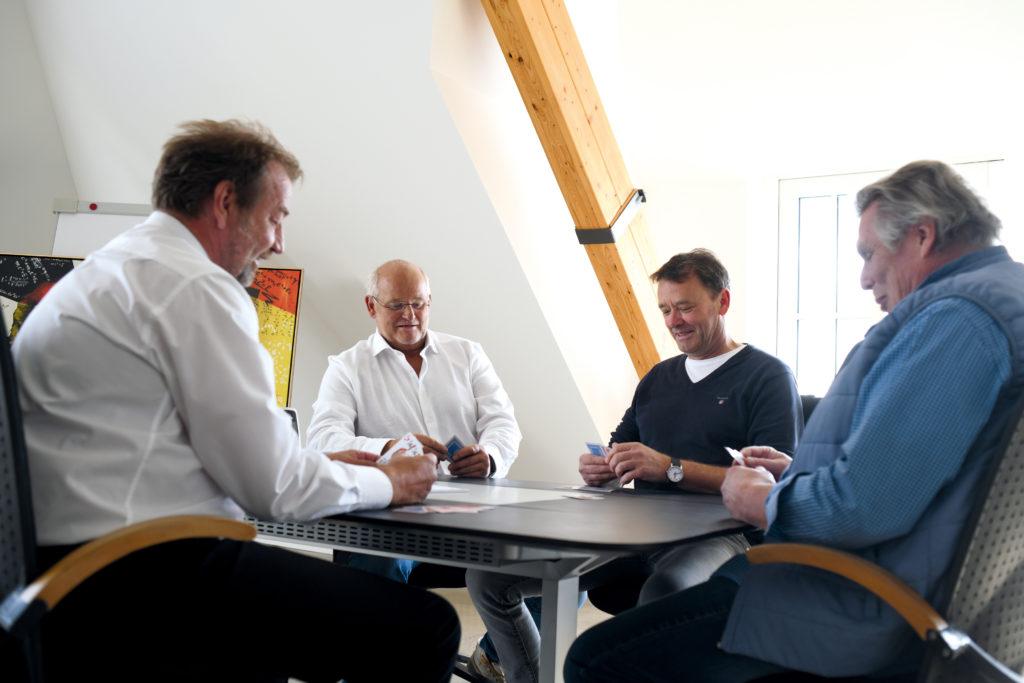 Jochen Twelker spielt Doppelkopf mit Martin Kapovits und Karl-Heinz Wohletz von der Kontorvier GmbH.