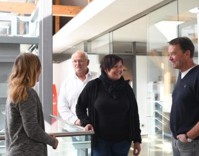Jochen Twelker (hinten links), Heidi Emmerich und Martin Kapovits (vorne rechts) stehen gemeinsam in einem großen Flur und unterhalten sich.