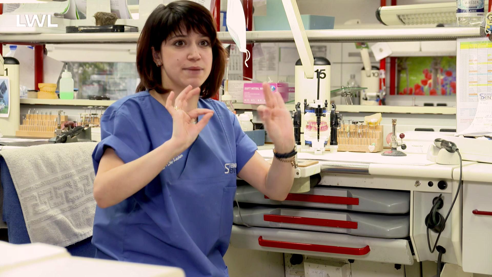 Eine gehörlose Zahntechnikerin des Dentallabors erklärt in Gebärdensprache etwas in die Kamera.