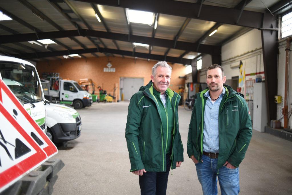 Thomas Pahls (links) und Christian Rüschoff stehen nebeneinander in grünen Arbeitsjacken in einer große Halle mit Autos und Verkehrsschildern und schauen in die Kamera.