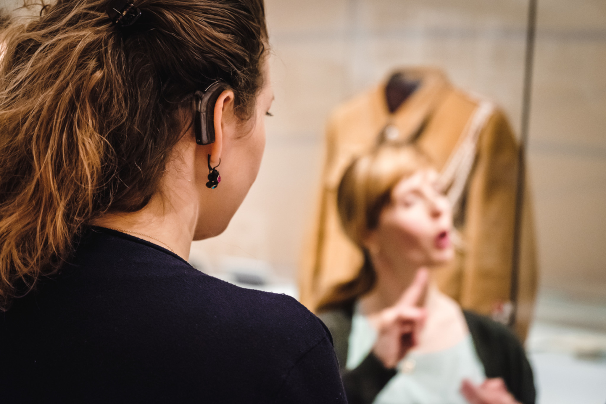 Eine Frau mit Hörgerät von hinten fotografiert, vor ihr sieht man eine zweite Frau, die in Gebärdensprache kommunziert.