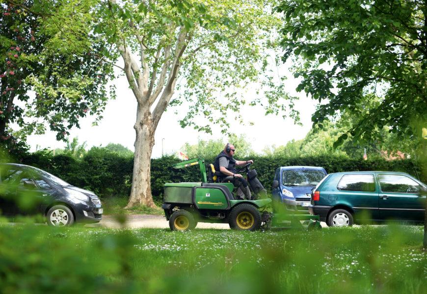 Ein Mitarbeiter der Grünbau fährt auf einem Mähtraktor an der Straße entlang, im Vordergrund eine grüne Wiese und Büsche.