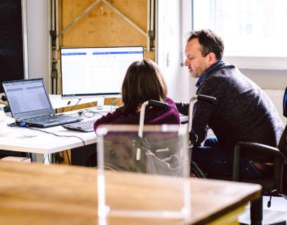 Eine Frau mit Rollstuhl und ein Mann sitzen gemeinsam im Büro vor einem Bildschirm und besprechen etwas.