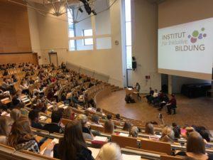 Blick in einen vollen Hörsaal der Europa-Universität in Flensburg, vorne vier Bildungsfachkräfte des Instituts für Inklusive Bildung, die die Vorlesung halten.
