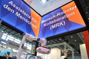 """Der IBG-Roboter im Vordergrund unter zwei großen Schildern: auf dem linken Schild steht """"Assistenz für den Menschen"""", auf dem rechten """"Mensch-Roboter-Kollaboration (MRK)""""."""