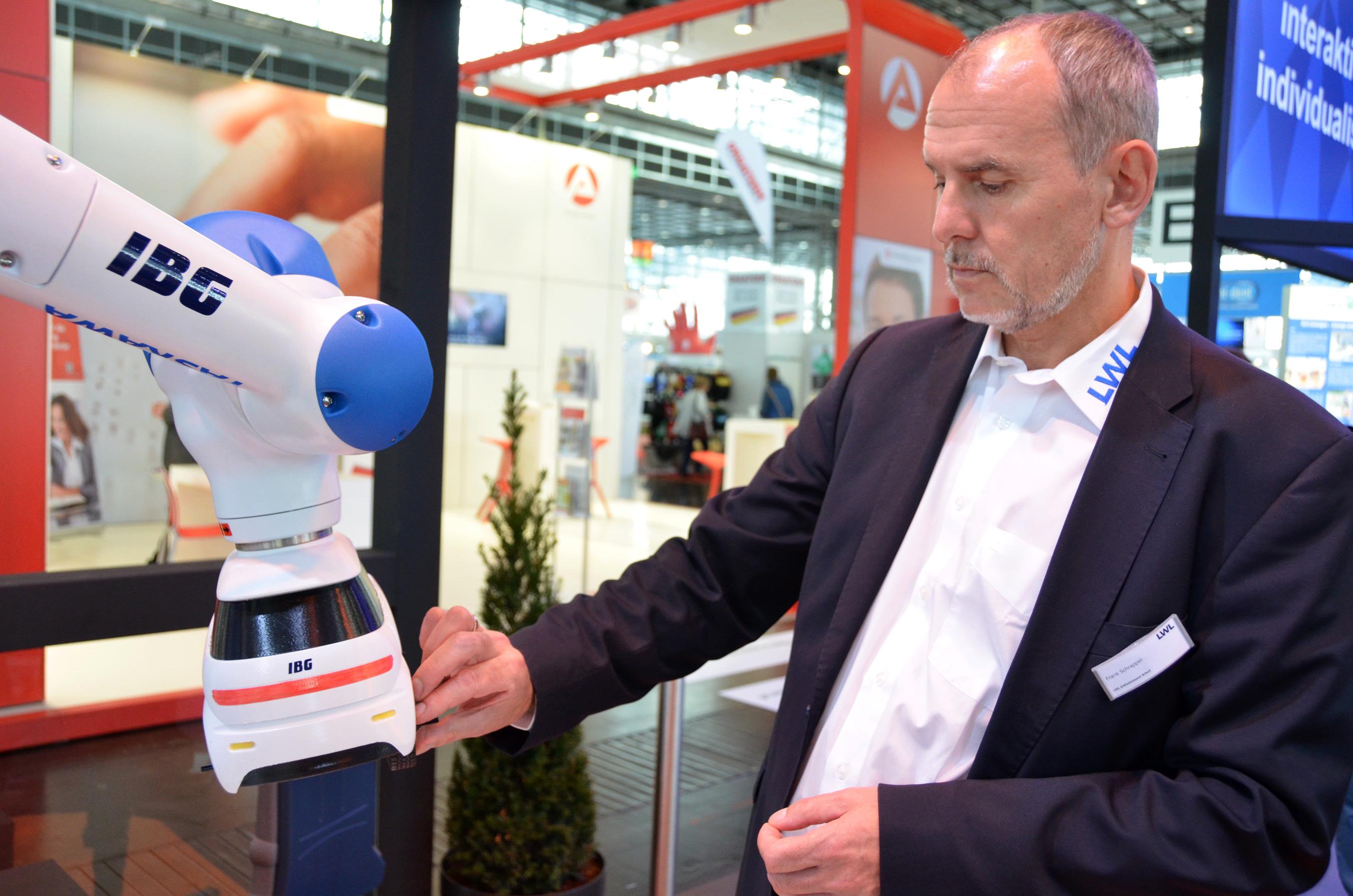 Frank Schrapper bedient gerade den Roboterarm und montiert ein Teil an einem Miniaturauto, das von dem Arm geführt wird.