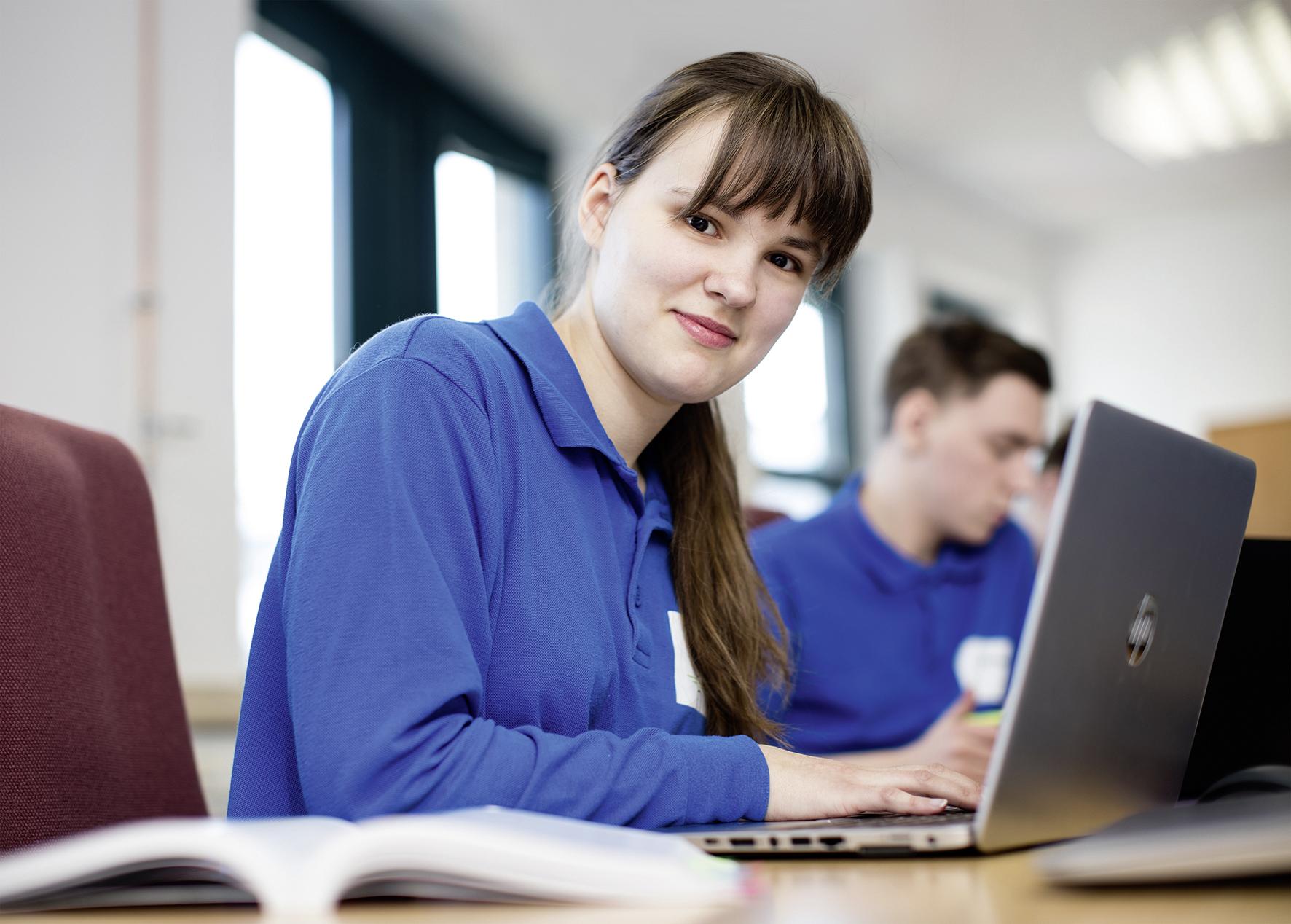 Eine junge Frau sitzt an einem Laptop und schaut in die Kamera.