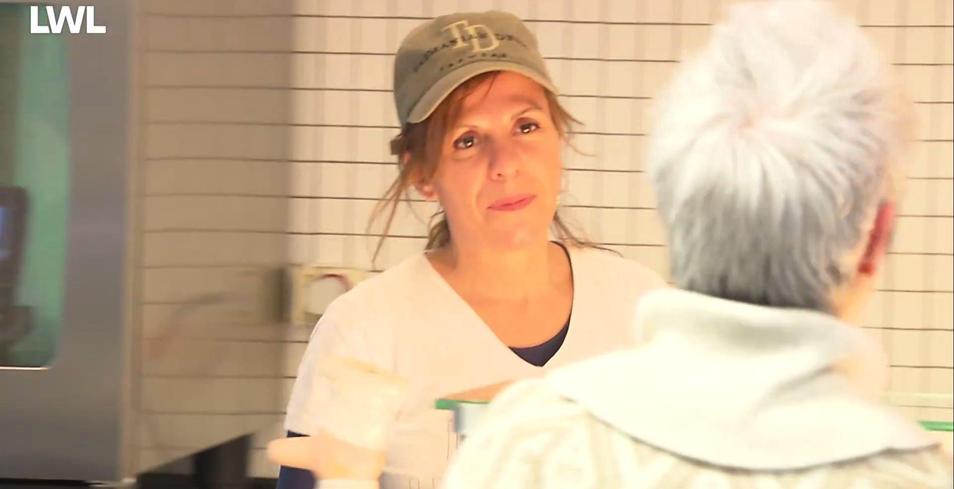 Eine Mitarbeiterin der AWO Service GmbH spricht über eine Theke mit einer Kundin, die nur von hinten zu sehen ist..