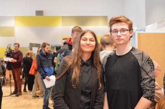 Eine Schülerin mit langen braunen Haaren und ein Schüler mit Brille schauen in die Kamera; sie stehen in einem Raum voller junger Menschen, die sich austauschen.