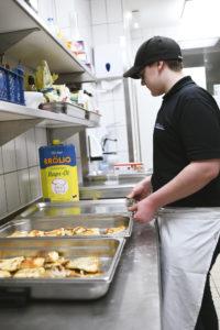 Ein Mitarbeiter steht in Arbeitskleidung in der Großküche; man sieht ihn von der Seite. Er schiebt gerade Edelstahl-Behälter nebeneinander, in denen geröstete Brotscheiben liegen.