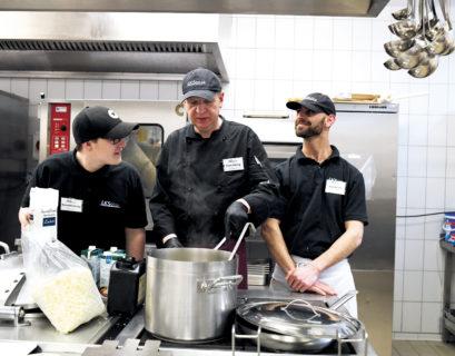 enedikt Minnig, Frank Kölling und Aqid Ibrahim (von links) stehen in Arbeitskleidung in der Großküche des Unternehmens hinter einem großen Kochtopf, Frank Kölling rührt, die drei sprechen lachend miteinander.