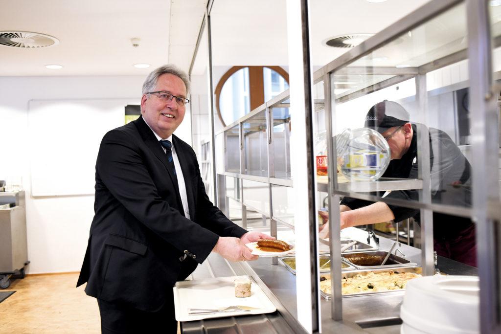 Jürgen Müller ist in Anzug und Schlips gekleidet; er nimmt an der Essenstheke der Kantine gerade einen Teller mit Currywurst von einem Küchenmitarbeiter entgegen und lächelt dabei in die Kamera.