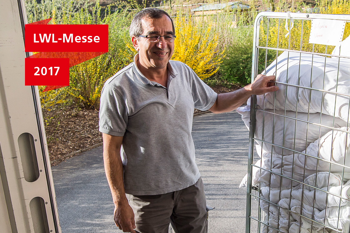 Ali Cütcü auf der Laderampe seines Lieferwagens neben einem Gitterwagen mit frischer Wäsche.