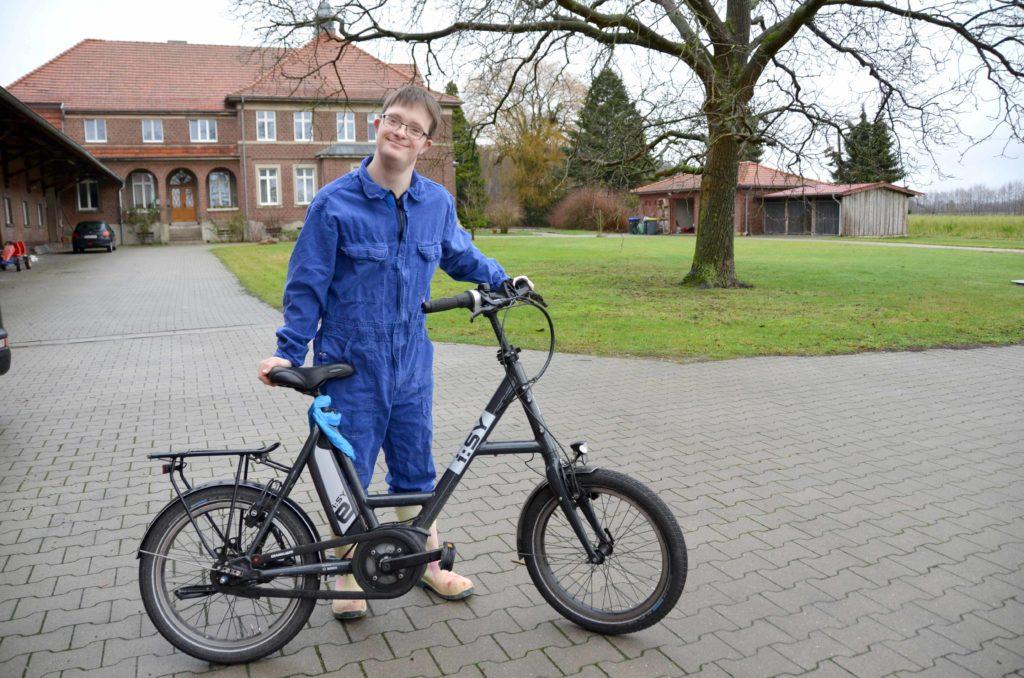 Tobias Koddebusch steht mit seinem Fahrrad auf dem Hof vor dem Stall und lächelt in die Kamera. Er trägt einen blauen Overall.