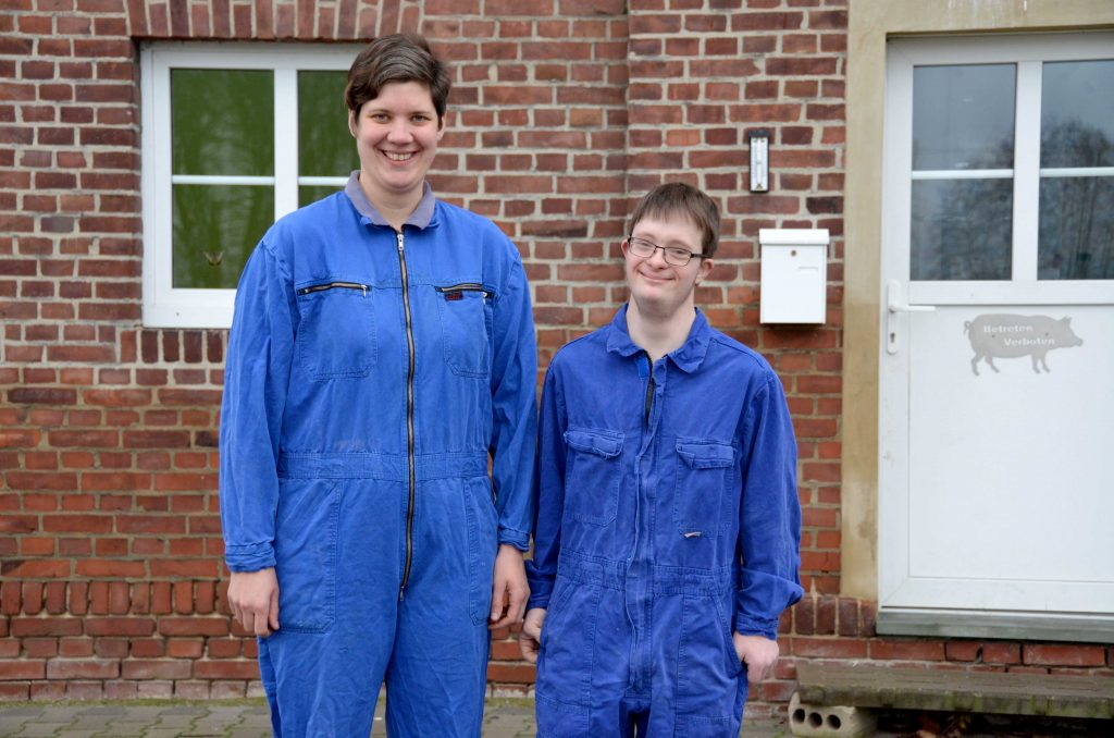 Silke Witte steht neben Tobias Koddebusch vor dem Haus. Beide tragen einen blauen Overall und lächeln in die Kamera.