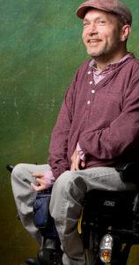 Lars Hemme sitzt in einem Rollstuhl und lächelt in die Kamera.