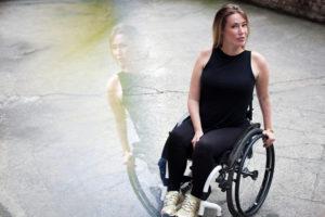 Die Autorin Laura Gehlhaar in ihrem Rollstuhl. Sie schaut in die Kamera.