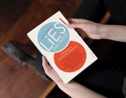 """Das Buch """"LiES"""" von oben fotografiert; eine Frau hält es in den Händen, das Gesicht der Person sieht man nicht."""