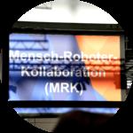 """Blau-orangefarbenes Schild, auf dem """"Mensch-Roboter-Kollaboration (MRK)"""" steht."""