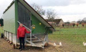 Ein Mitarbeiter des Erlebnis-Bauernhofs steht auf einer Wiese vor einem mobilen Hühnerstall und schaut in die Kamera.