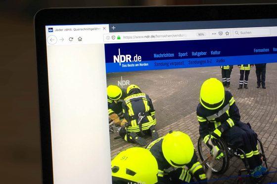 Foto der NDR-Seite, auf der der Video-Beitrag zu sehen ist. Das Standbild zeigt Finn-Niklas Gerken in Feuerwehrkleidung in seinem Rollstuhl, umgeben von seinem Team.