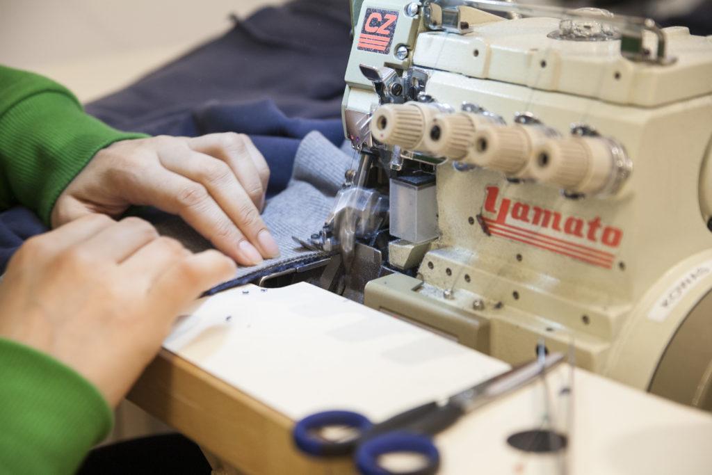 Eine Nähmaschine und die Hände einer Person, die gerade ein Stoffstück näht.