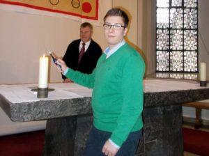 Niklas Grewing zündet eine Kerze auf dem Altar der Kirche an und schaut in die Kamera.