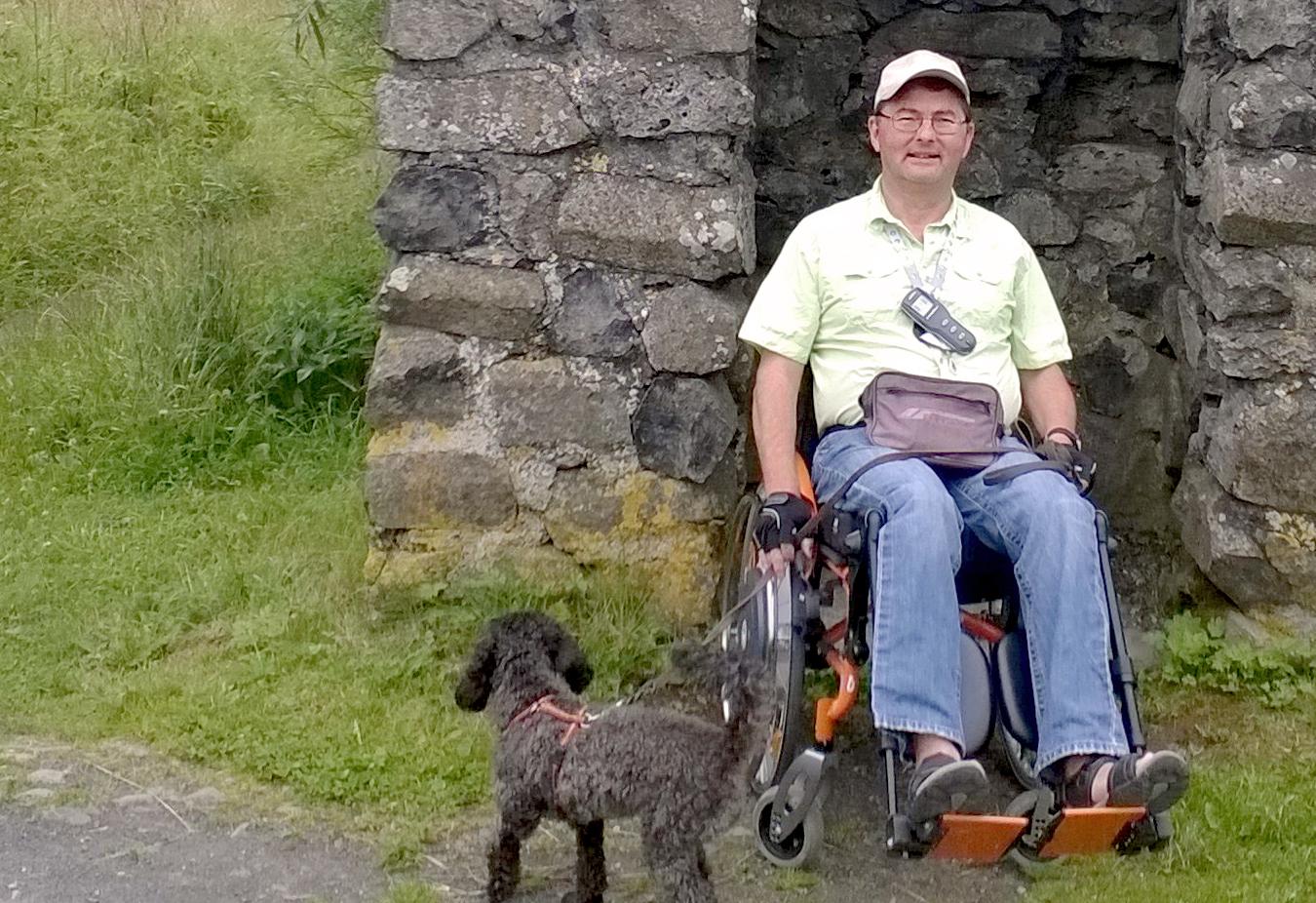 Norbert Sandmann mit Rollstuhl und Hund unterwegs in der Natur.