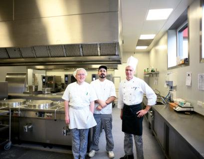 Drei Mitarbeiter der Integrationsküche Nordkirchen (links: Torsten Wißmann) stehen in Arbeitskleidung in der Großküche und schauen in die Kamera.