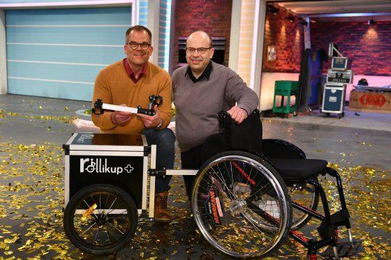 Andreas Neitzel (links), Eduard Wiebe (rechts) posieren mit einem Rollstuhl samt Rollikup und Anhänger nach der Show auf der Bühne.