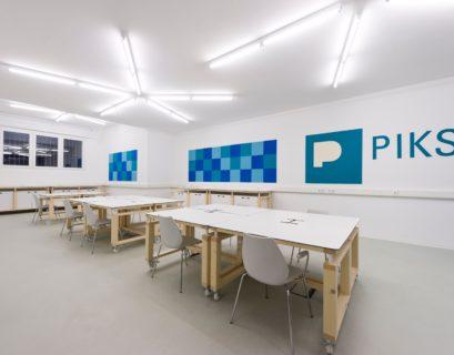 """Blick in einen hellen, leeren Raum des """"PIKSL Labor"""" in Düsseldorf, in dem mehrere Tische und Stühle stehen."""