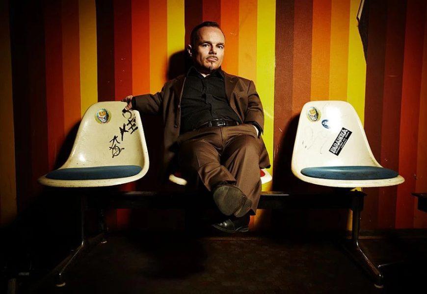 Peter Brownbill sitzt in einem braunen Anzug auf einem Stuhl vor einem bunten Hintergrund, die Beine lässig hochgelegt.