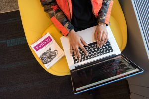 Die Hände einer Frau auf der Tastatur eines Laptops von oben, neben ihr liegt ein Buch zu einer Programmiersprache.