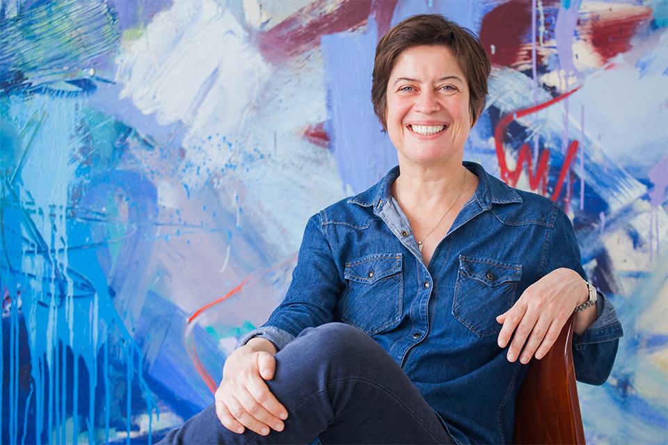 Stefanie Trzecinski sitzt mit angewinkeltem Bein auf einem Stuhl vor einer bunten Wand und lächelt.