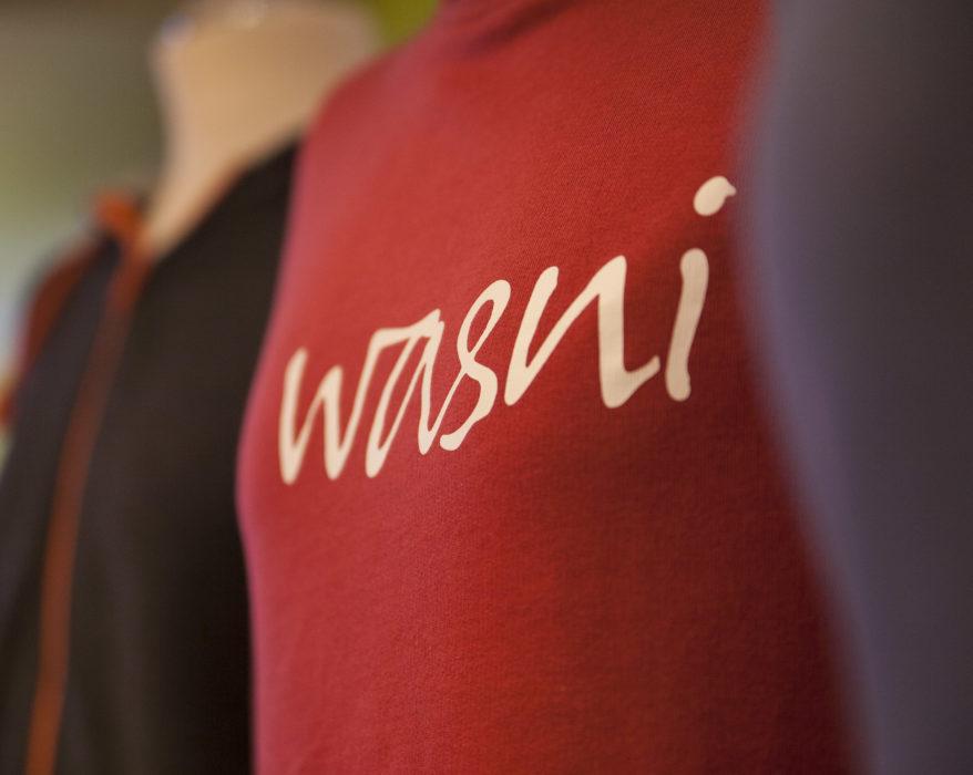 """Bunte Pullis auf Schneiderpuppen, in der Bildmitte ein roter Pulli, auf dem """"wasni"""" steht."""