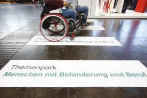 """Bodenbeschriftung """"Themenpark Menschen mit Behinderung und Beruf"""", über die gerade ein Rollstuhlfahrer fährt."""