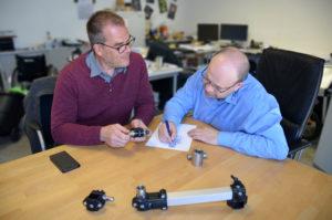 Andreas Neitzel und Eduard Wiebe tüfteln an einem runden Tisch in ihrem Büro an der Anhängerkupplung.