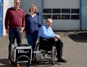 Andreas Neitzel, Ines Rose und Eduard Wiebe (er im Rollstuhl mit Rollikup) posieren draußen vor dem Firmengebäude der TeutoInServ gGmbH.